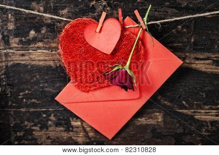 Red  hearts, rose and envelop  hanging on the clothesline. On old wood background