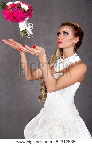 Portrait Of A Young Attractive Bride Throwing A Bunch Of Flowers