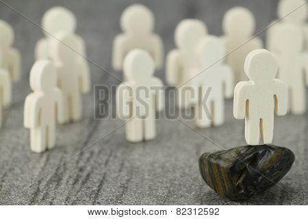 Gruppe mit Holzfiguren und einem Redner