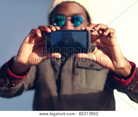 Technology And People Concept - Modern Stylish African Man Makes Selfie, Screen Front View