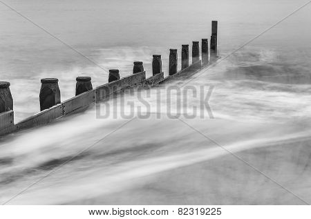 Milky white waves splashing against wooden barrier