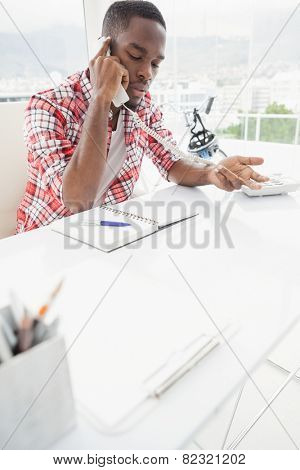Concentrated businessman phoning and gesturing in the office