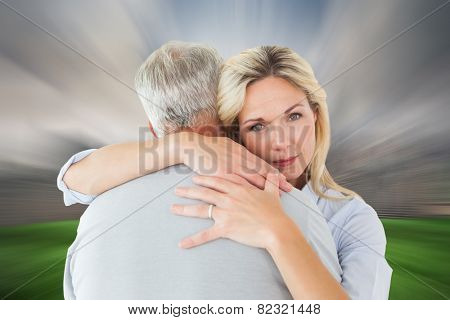 Unhappy blonde hugging her husband against cloudy sky over city