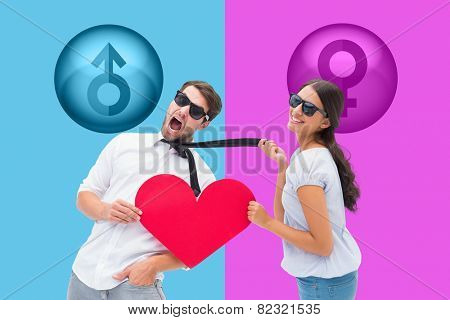 Brunette pulling her boyfriend by the tie holding heart against pink and blue