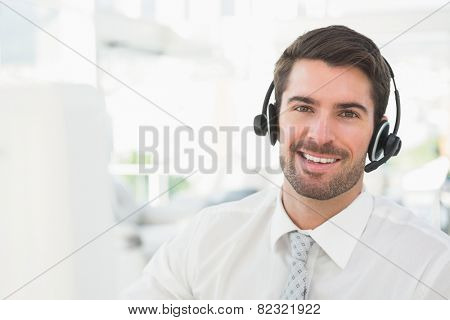 Handsome businessman with headset interacting in his office