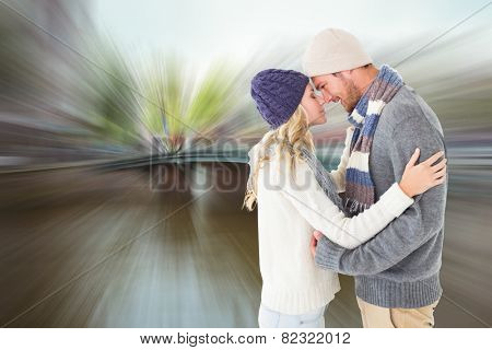 Attractive couple in winter fashion hugging against canal in amsterdam