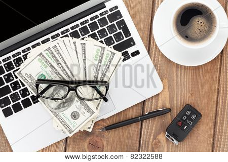 Office table with pc, coffee cup, glasses and money cash. View from above