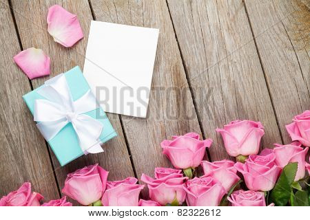 Pink roses and valentines day greeting card or photo frame and gift box over wooden table. Top view with copy space