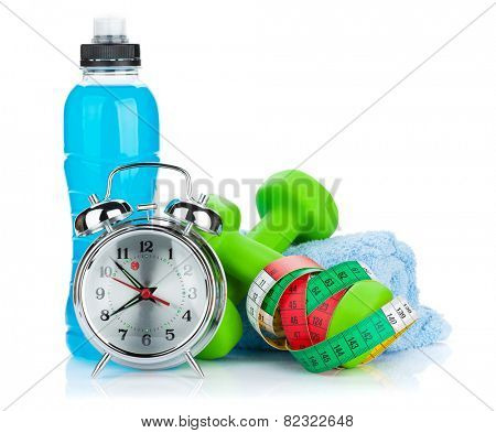 Two green dumbells, tape measure, drink bottle and alarm clock. Fitness and health. Isolated on white background