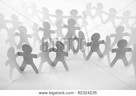 Teams of paper doll people holding hands