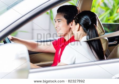 Asian couple driving new car on driveway to their home