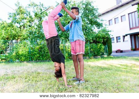 Brother and sister, two black children, playing in garden doing handstand