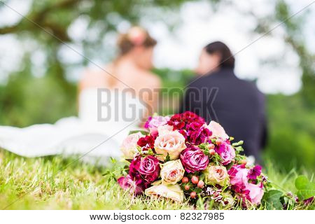 Wedding couple of bride and groom sitting on the meadow with bridal bouquet behind them, candid shot