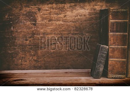 grunge books on wooden shelf with space for your background.