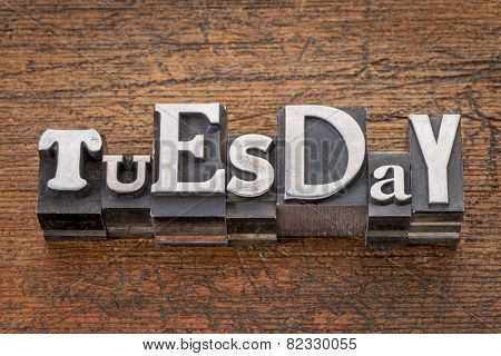 Tuesday word in mixed vintage metal type printing blocks over grunge wood