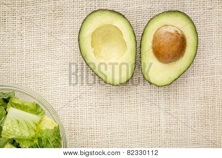 halved avocado and a bowl of romaine lettuce against burlap canvas