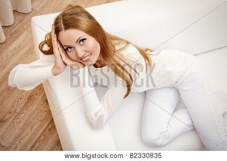 Happy young woman resting at home in a comfortable sofa.