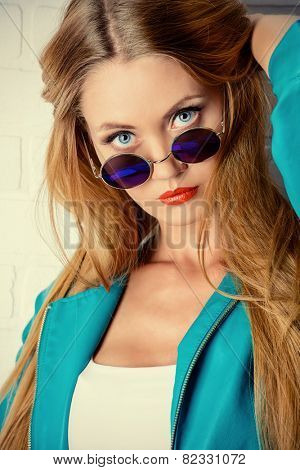 Close-up portrait of a stunning young woman wearing round sunglasses. Jeans style. Beauty, fashion.