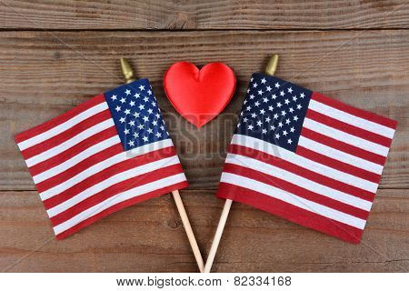 High angle shot of two crossed American flags on a rustic wood surface with a red heart inbetween. Horizontal format.