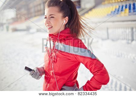 Girl with mobile phone in activewear spending leisure at stadium