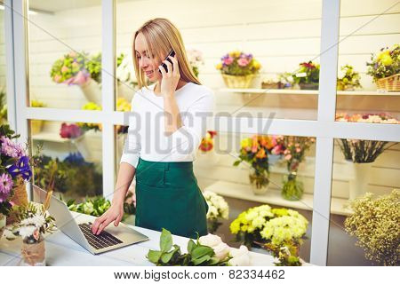 Pretty shop assistant speaking on the phone and using laptop in flower shop