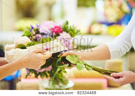 Female florist selling bunch of white roses