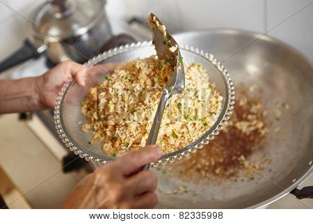 Finish cooking the friend rice and lift it up on a plate, focus on the spatula might have some blur movement