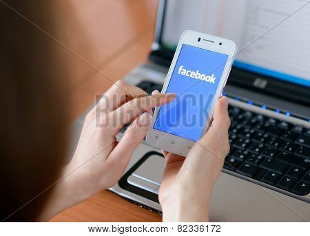 ZAPORIZHZHYA, UKRAINE - JANUARY 23, 2015: Young Woman Using Facebook Social Network Application on her Smart Phone.