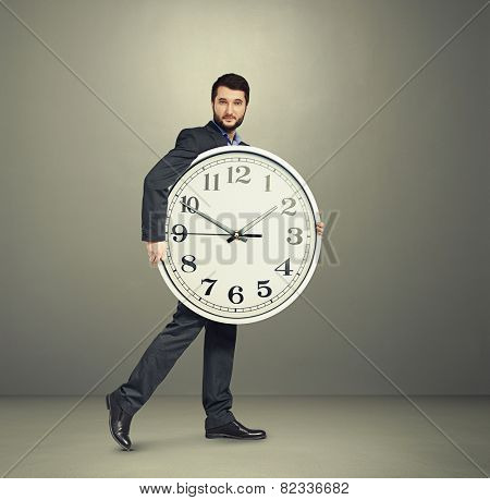 serious businessman with big white clock going forward over grey background
