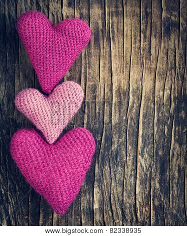Three Crochet Pink Hearts On Wooden Background
