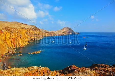 Quiet ocean cove on the island of Madeira. White sailing yachts lit sunset. Calm on the Atlantic Ocean