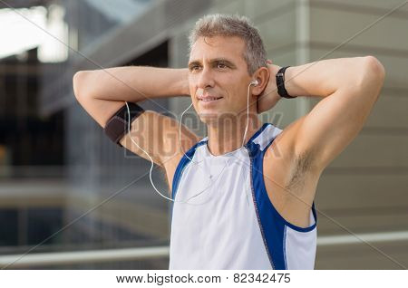 Portrait Of Relaxed Mature Man Enjoying Music On Earphones
