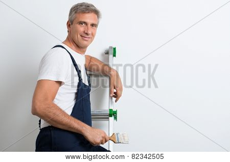 Happy Mature Painter Standing On Stepladder Holding Brush