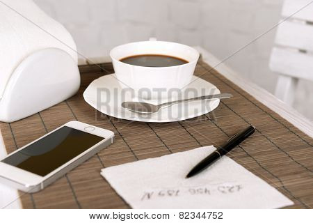 Cup of coffee with mobile phone, pen and phone number on napkin on table with bamboo mat and white wall background