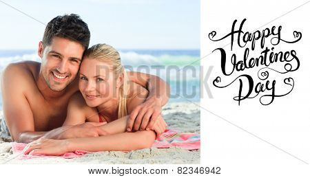 Lovers lying down on the beach against happy valentines day