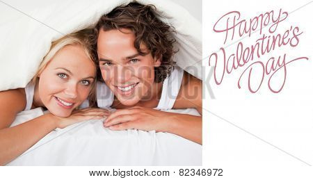 Couple under a duvet against cute valentines message