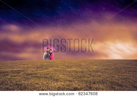 Couple standing underneath an umbrella against aurora night sky in purple