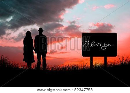Happy hipster couple holding hands against red sky over grass