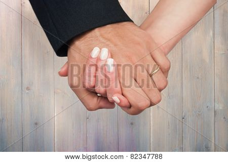 Newlyweds holding hands close up against pale grey wooden planks