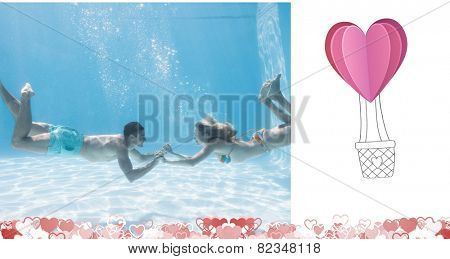 Cute couple holding hands underwater in the swimming pool against heart hot air balloon