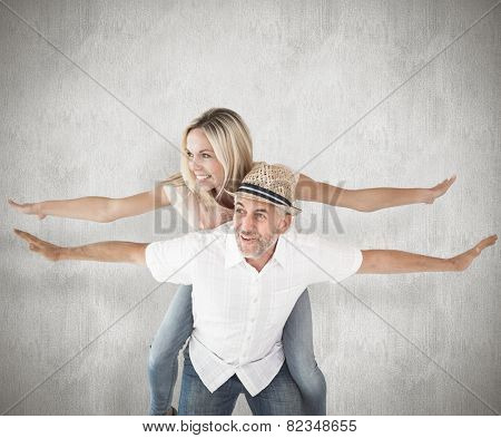 Happy man giving his partner a piggy back against weathered surface