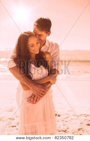 Affectionate couple cuddling at the beach
