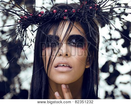 pretty brunette woman with make up like demon at halloween, clos