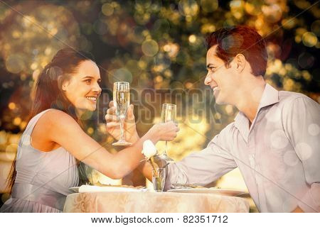 Smiling young couple with champagne flutes sitting at an outdoor caf�?�©
