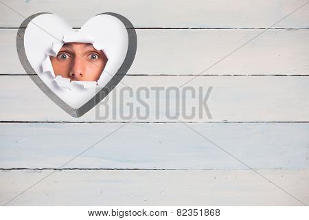 Young man looking through paper rip against heart in wood