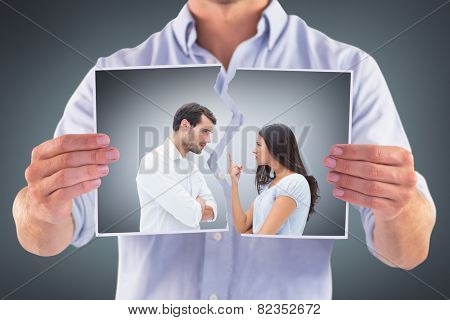Angry couple facing off during argument against grey vignette