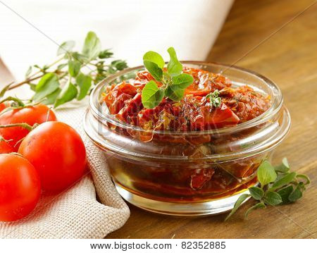sun-dried tomatoes with herbs in a glass jar