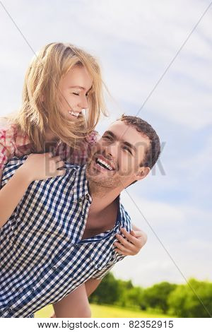 Portrait Of Happy And Cheerful Young Caucasian Couple Piggybacking Outdoors.summer Vacations And You