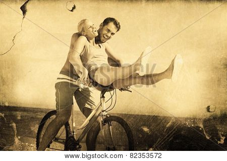 Happy man giving girlfriend a lift on his crossbar against grey background