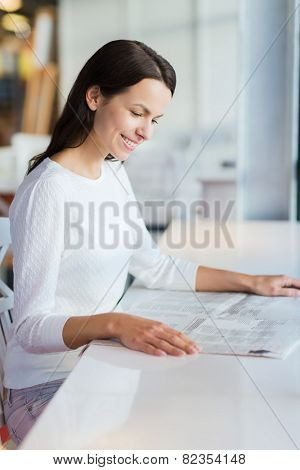 leisure, information, mass media, people and lifestyle concept - smiling young woman reading newspaper at cafe
